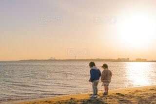 夕暮れに海を見つめる子供達の写真・画像素材[4148302]