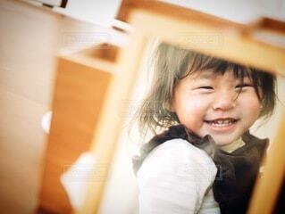 鏡を見せると笑顔になる女の子の写真・画像素材[4149422]