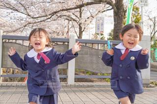 桜の下で走る制服の兄妹の写真・画像素材[4320224]