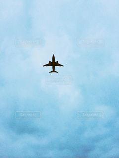 曇りの青い空を飛んでいるジェット大型旅客機の写真・画像素材[1313300]