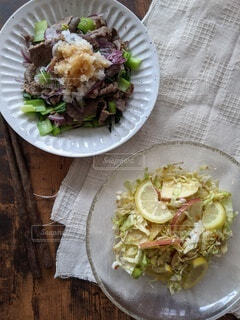 テーブルの上にサラダとお肉料理の写真・画像素材[4338541]