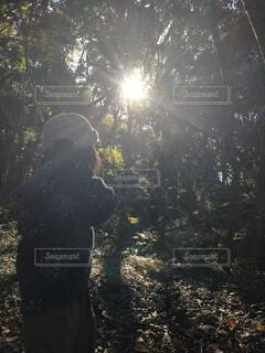 夕日の前に立っている人の写真・画像素材[4154211]
