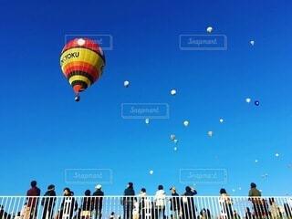 空に凧を飛ばす人々のグループの写真・画像素材[4154247]