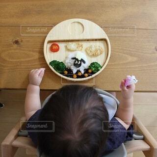 テーブルの上に座っている小さな子供の写真・画像素材[4154245]