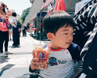 ポップコーンを前に薄笑う幼児の写真・画像素材[1164322]
