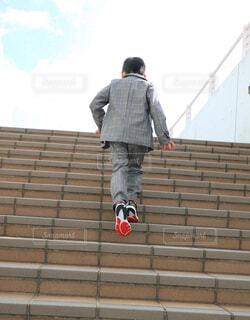 スーツで階段を駆け上がる男の子の写真・画像素材[4224879]