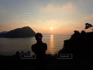 夕焼けを見る男の写真・画像素材[4322636]