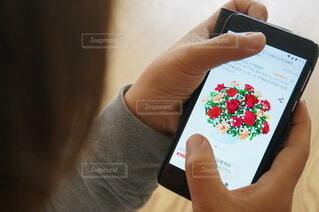 県外の母へフラワーギフトを注文する女性の写真・画像素材[4400592]