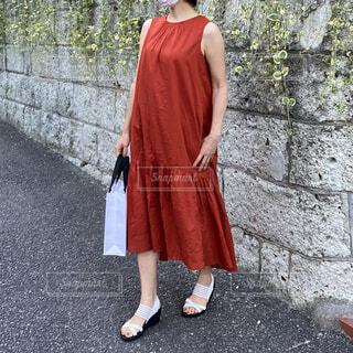 壁の前に赤いノースリーブのドレスで立つ女性の写真・画像素材[4709355]