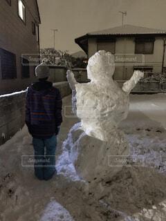 巨大雪だるまと背比べする子供の写真・画像素材[4179586]