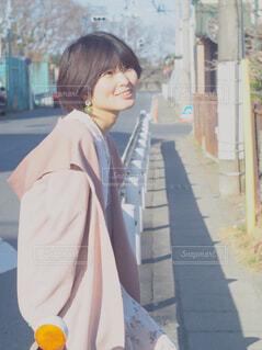 女性,風景,春,屋外,コート,爽やか,人物,人,笑顔,風,歩道,通り,通学路,ガードレール,住宅地,ストリートファッション,人間の顔