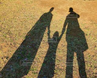夕暮れの公園で家族3人で影の伸びを楽しむの写真・画像素材[4461020]
