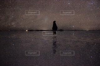 ウユニ塩湖の満点の夜空の下に立つ男性の写真・画像素材[4793515]