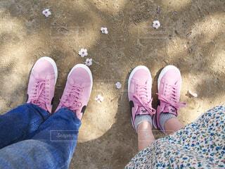 桜の季節にピンクのおそろいのスニーカーを履いた足元の写真・画像素材[4238373]