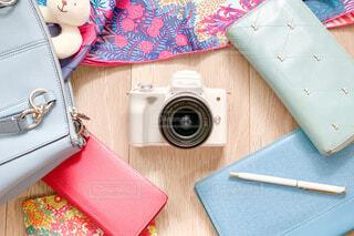 ミラーレスカメラを中心に広がる女性のバッグの中の小物の写真・画像素材[4243075]