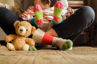 ママの膝に座っているおそろいの靴下を履いた赤ちゃんの足元のクローズアップの写真・画像素材[4250147]