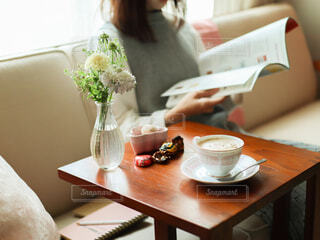 本を読んでる人の隣に置かれたコーヒーの写真・画像素材[4312757]