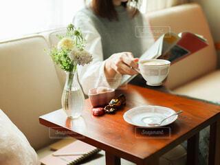 本を読みながらコーヒーを飲む人の写真・画像素材[4312758]