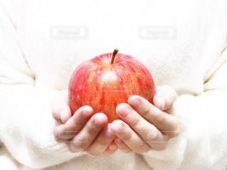 リンゴを持っている手の写真・画像素材[927707]