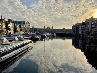 夕焼けに染まる水の都オランダ、アムステルダムの中央駅の写真・画像素材[4313903]