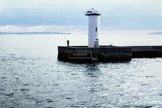 風景,海,空,屋外,湖,綺麗,一人,水面,美しい,人,灯台,釣り,趣味,のんびり,寂しい,楽しみ,日中,白い灯台,釣り師,魚を釣り
