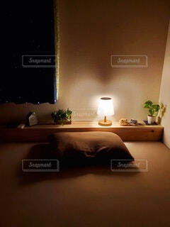 暗い部屋のベッドに座っているランプの写真・画像素材[4368943]