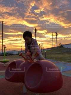 夕日の前に座っている人の写真・画像素材[4643933]