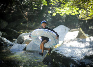 岩の上にサーフボードに乗っている男の写真・画像素材[4372520]