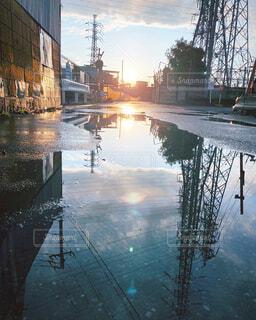 空,夕日,雨,屋外,雲,水たまり,水面,反射,都会,電波塔,雨上がり