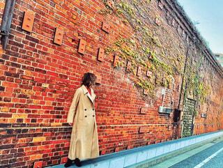 レンガの壁の前に立っている男の写真・画像素材[4386616]