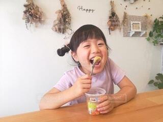 食べ物を食べるテーブルに座っている小さな女の子の写真・画像素材[4793762]