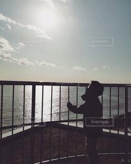 夕日と海を眺める少年の写真・画像素材[4370911]