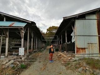 古い鶏舎の前に立つ男の子の写真・画像素材[4370919]