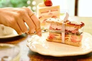 窓際の席にある皿の上のケーキ ハサミでリボンを切るの写真・画像素材[4392989]