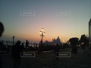 夕日の前の通りを歩いている人々のグループの写真・画像素材[4377913]