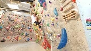 ボルダリングスクールで登り続ける少年の写真・画像素材[4401999]