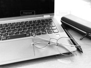 テーブルの上にノートパソコンと眼鏡の写真・画像素材[4401395]