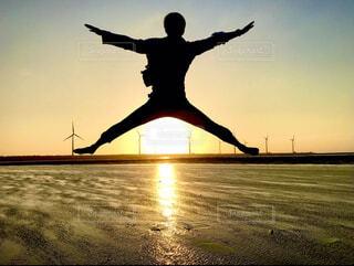 夕陽が映る海の上でジャンプする男性のシルエットの写真・画像素材[4401604]