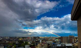 雨上がりの曇天と青空の間から見える虹の写真・画像素材[4410953]