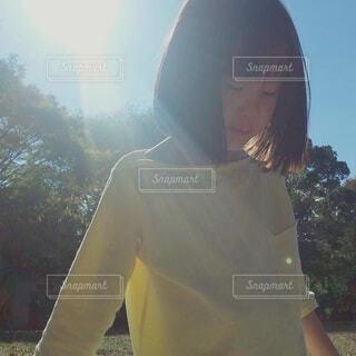 陽射しを背中にあびて下を向いている女の子の写真・画像素材[4408344]