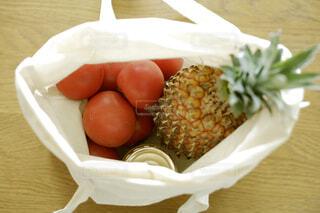 ダイニングテーブルの上のトマトとパイナップルとジャムが入ったエコバッグの写真・画像素材[4418226]