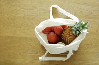 ダイニングテーブルの上のトマトとパイナップルとジャムが入ったエコバッグの写真・画像素材[4418227]