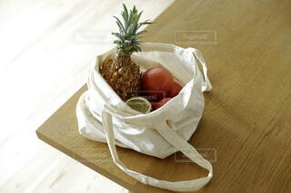 野菜や果物が入っている木製テーブルの上の布製バッグの写真・画像素材[4419161]