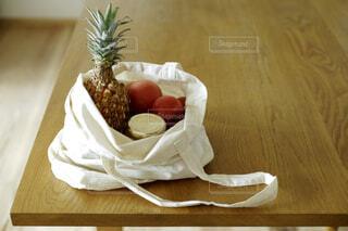 野菜や果物が入っている木製テーブルの上の布製バッグの写真・画像素材[4419162]