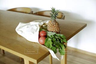 野菜や果物が入っている木製テーブルの上の布製バッグの写真・画像素材[4419176]
