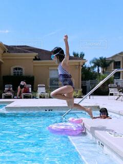 夏の日にプールに飛び込む水遊びしている女の子の写真・画像素材[4430667]
