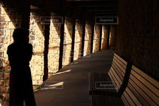 レンガの壁の隣に立っている人の写真・画像素材[4407401]