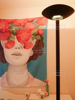 アート系ファブリックポスター(女性)を照らすスタンドライトの写真・画像素材[4583648]