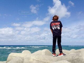 沖縄の海を見ながら風に吹かれる男の子の写真・画像素材[4626811]