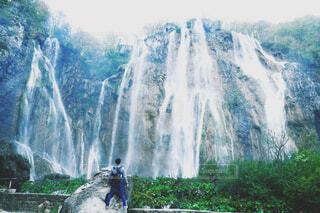 大滝の前に立つ男の写真・画像素材[4431673]